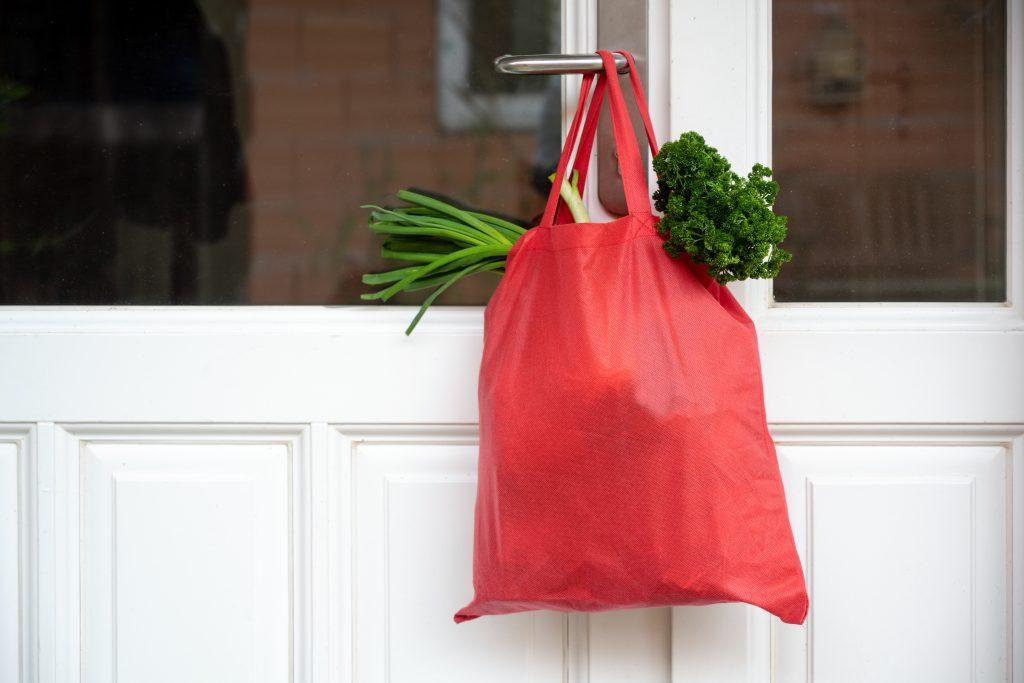 Gefüllte rote Einkaufstasche mit Gemüse zur Illustration von Alltagsbegleitung