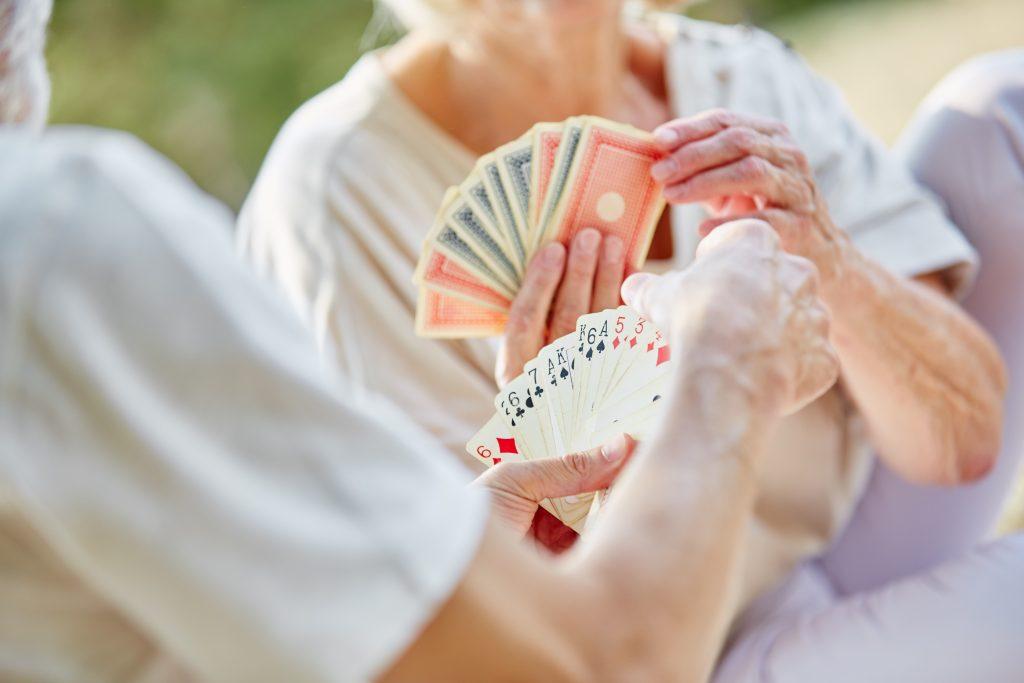 Seniorin und Alltagsbegleiterin beim Kartenspielen zur Illustration von Einzelbetreuung