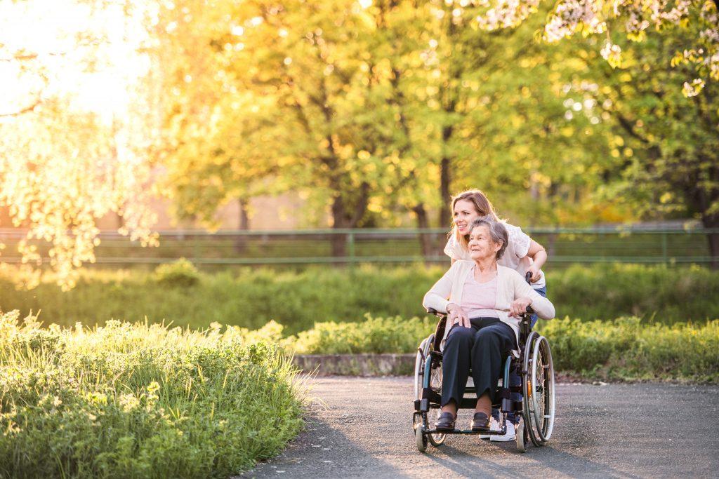 Alltagsbegleiterin beim Spaziergang mit Seniorin im Rollstuhl zur Illustration von Pflegebegleitung