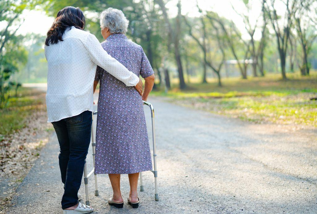 Alltagsbegleiterin und Seniorin mit Rollator beim Spaziergang